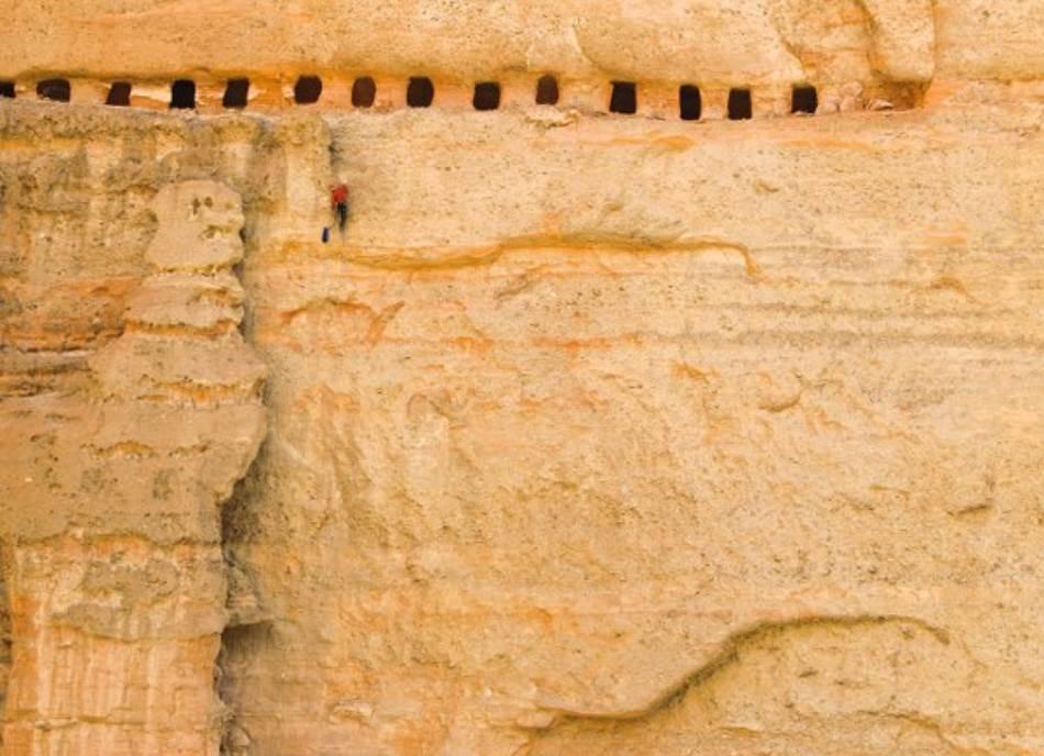 Da bi stigao do niza pećina iskopanih u litici na visini od 47 metara, Met Sigal (gore) vere se uz stenu koja je toliko trošna da se odronjava na najmanji dodir. Pećine stare 800 godina sada su prazne, ali u njima su nekada možda bili pohranjeni rukopisi. Ted Heser (levo) uspinje se do ulaza u pećinu.