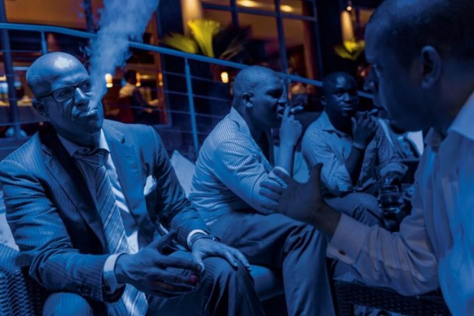 Mladi biznismeni iz Cigar kluba u Lagosu, koji se ubrajaju u sve brojniju višu građansku klasu, uživaju u trenutku opuštanja uz cigaru u jednom hotelu na ostrvu Viktorija.