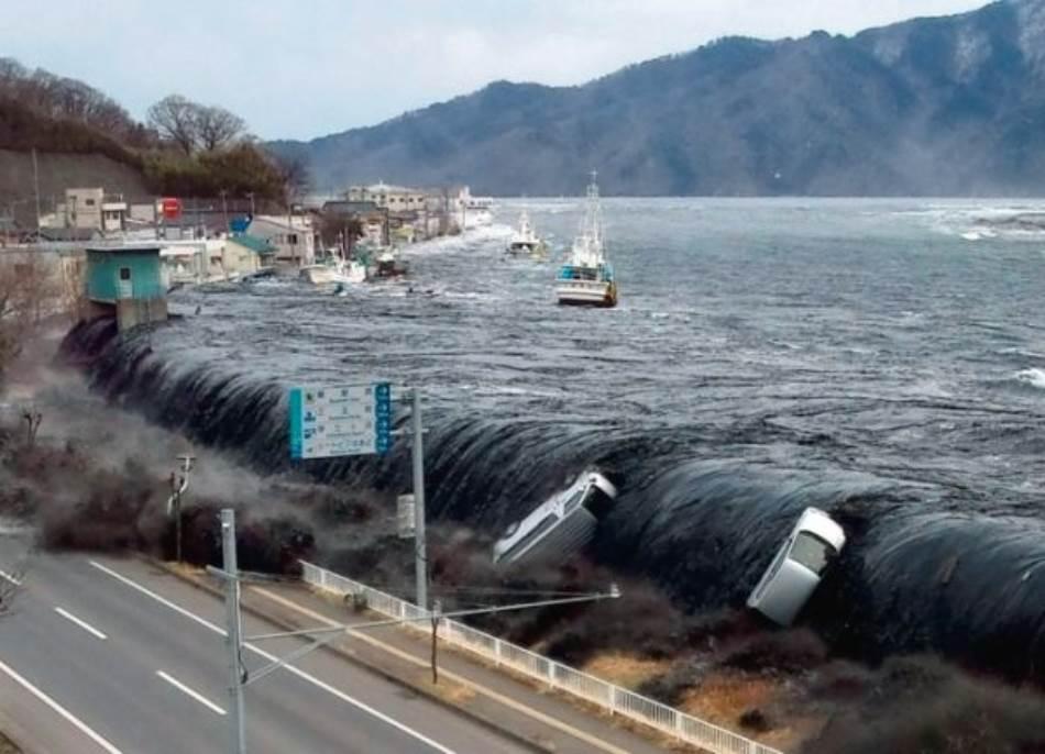 Crn od mulja koji je pokupio u luci, prvi talas cunamija se preliva preko zaštitnog bedema u Mijaku, noseći kombije i brodove. Japanska odbrana nije bila spremna za talase daleko više od onih koje su naučnici predvideli.