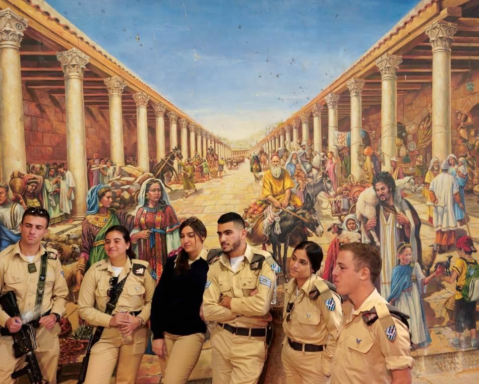 Izraelski vojnici slušaju vodiča na jerusalimskom Kardo maksimusu, ili rimskoj glavnoj ulici, gde mural prikazuje prometnu ulicu s kolonadama, kako je verovatno izgledala u vizantijsko vreme, u šestom veku – saizuzetkom dečaka s bejzbol kačketom.