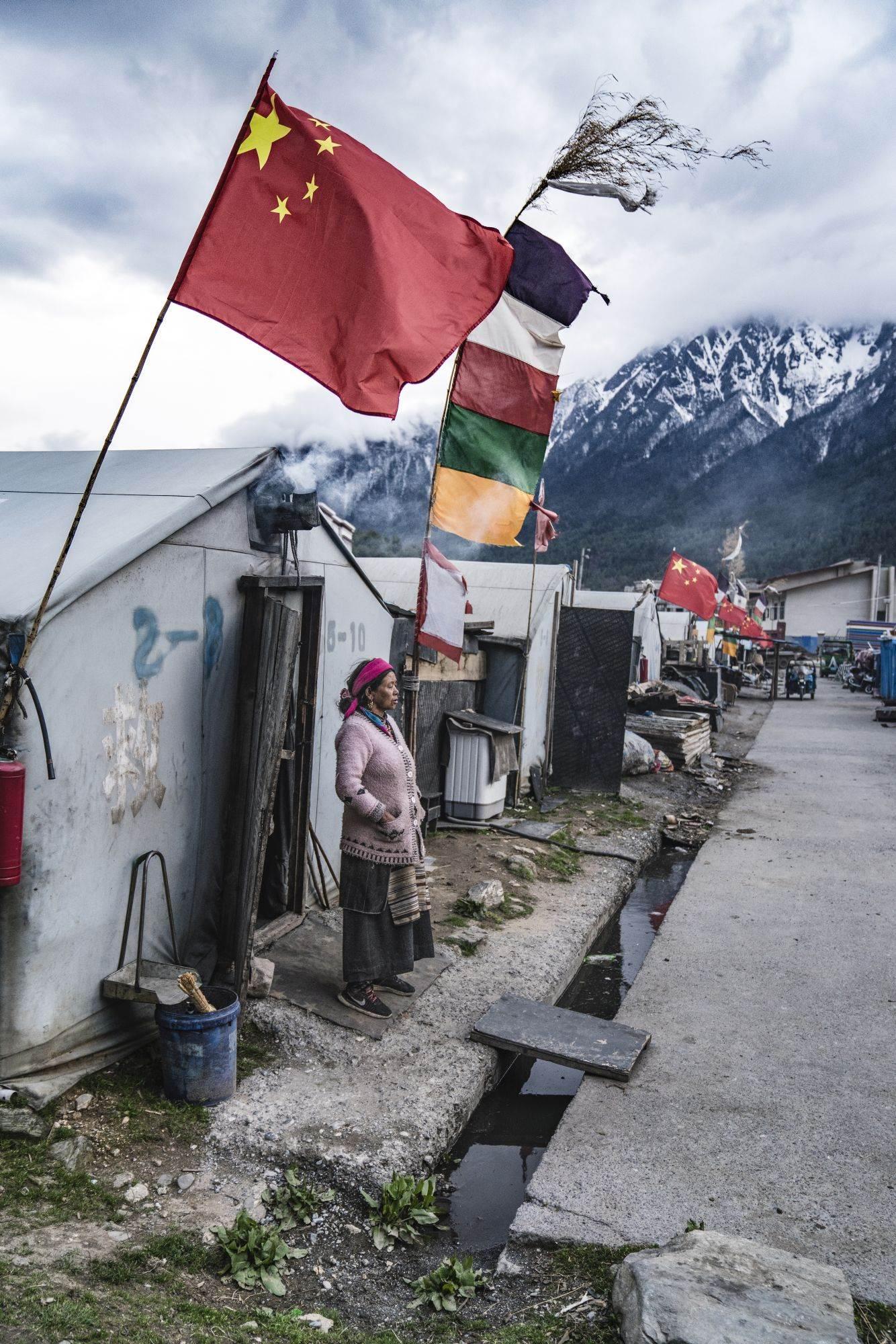 Kineska zastava vijori se rame uz rame sa tibetanskim bojama u planinskom selu Đirong, prvom kineskom gradu u koji je tim ušao nakon napuštanja Nepala. Kineska vlada je decenijama podsticala tibetanske nomade da se naseljavaju u gradovima poput Đironga. Šatorski grad u gradu prihvata ljude raseljene snažnim zemljotresom 2015. godine.