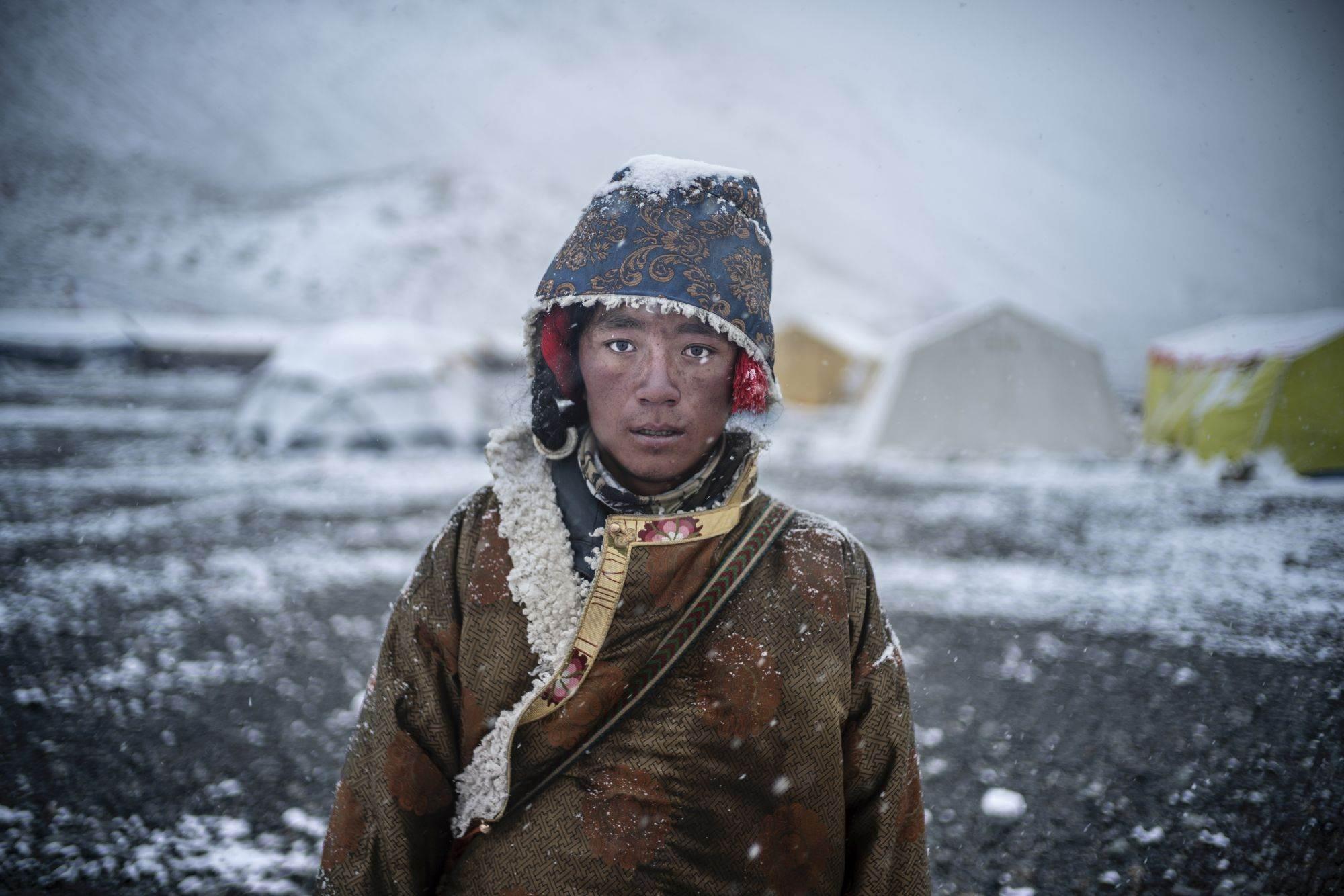 Mladi vozač tibetanskog jaka prolazi kroz kineski bazni kamp Everest tokom snežne kiše nakon dugog dana dovlačenja zaliha na gornju planinu. Mnogi vozači jakova žive u selima na severu koja zavise od prihoda od penjačkih ekspedicija. Njihove životinje i dalje su ključne za penjanje na kineskoj strani Everesta.