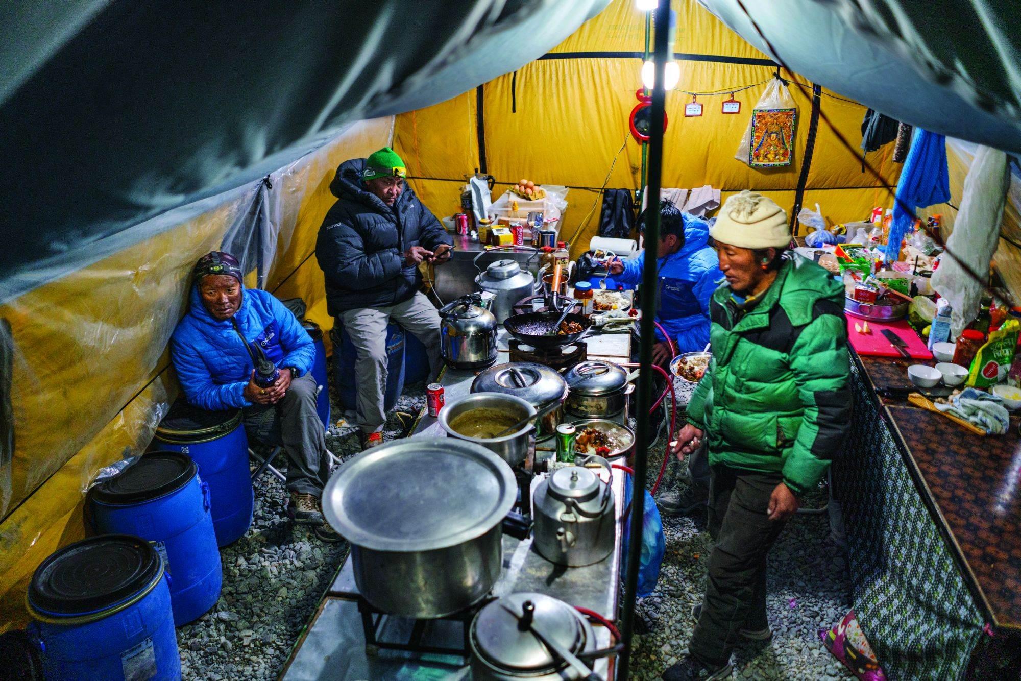Nakon gužve oko večere ekipa kuvara odmara se s gostima. Nepalski kuvar Bire Tamang (pozadi desno) i njegov tibetanski pomoćnik Čhumbi (desno) pripremaju ukusna jela od pirinča i sočiva, supu i knedle za 30 do 40 ljudi dnevno, uključujući i Da Geldže (Dava) Šerpu (pozadi levo), koji je vođa ekipe nosača, i Pasang Gomba Šerpu, privatnog vodiča.