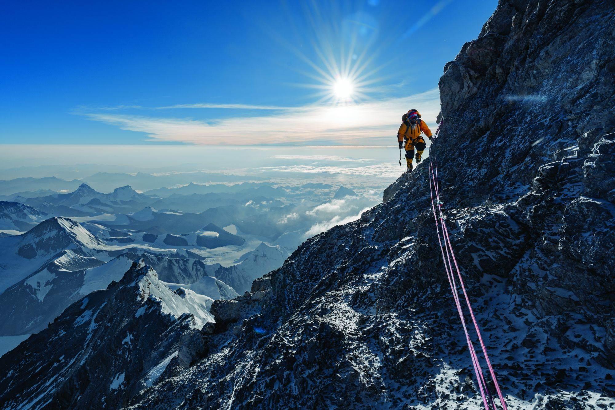 Pasang Kadži Šerpa prati fiksirane konopce preko jednog stenovitog prevoja nedaleko od vrha Everesta. Tog dana kad je ekipa stigla na vrh, bili su jedini penjači na obe strane planine.