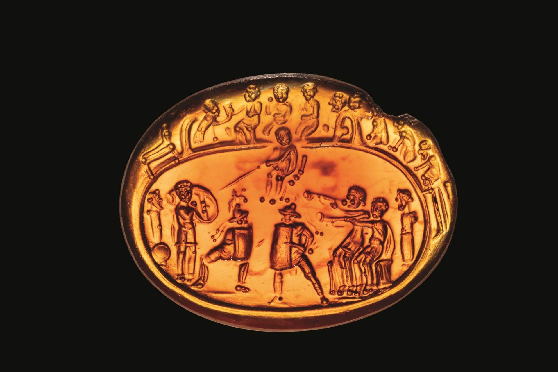 Gladijatori, okruženi duvačima u rog i navijačima, sukobljavaju se sa palicom sudije. Ugraviran u prvom veku u dragom kamenu veličine nokta na palcu, prizor dočarava spektakl starih igara.